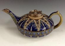 A Royal Doulton Lambeth compressed teapot, decorated in relief with blue an