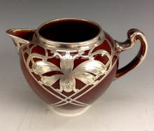 An American Art Nouveau Lenox pottery jug, overlaid in silver with iris and