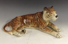 A Bretby model of a recumbent lion, he lays stretching his hind legs and pa