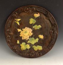 A large Bretby circular plaque, decorated in relief with a lotus flower and