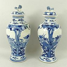 A pair of 19th century Chinese porcelain blue and white vases and covers of baluster form, decorated with birds amongst trees, base bears four character Kangxi mark, 19cm high.