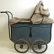 A 1940's doll's pram with a blue chassis and canvas hood and apron, together with two bisque headed dolls, the one with 'Made in England BA/2' mark, the other a baby doll, both 40cm high. (3)