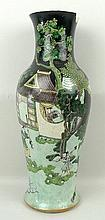 A 19th century Chinese famille noire porcelain baluster vase, decorated with five figures including farmers and fisherman, visiting a scholar at his home, set amongst a tree filled garden with hills behind, painted two character mark to base, 45cm