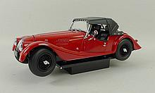 A quantity of Minichamps models, scale 1:18, including a Morris Minor Cabriolet, a Model Icons Jaguar Mark 2, Kyosho Morgan 4/4 Sport in red, a Ricko Austin 7 De Luxe Saloon 1932, three Minichamps showcases, and a Minichamps showcase containing a