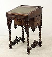 A Pugin style burr walnut piano top Davenport desk, with green leather skiver, the top opens to reveal an interior with three small drawers, two drawers to the side, the Gothic style arch apron front flanked by blind fret carving adjoining