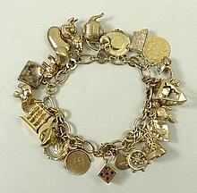 A 9ct gold oval link charm bracelet on a bolt ring clasp wit