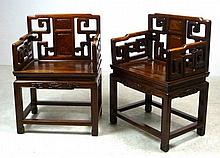 A pair of 19th century Chinese hardwood open armchairs, with burr walnut panels to the pierced back rests, decorated with geometric scrollwork, raised on square section legs joined by peripheral stretchers, 50 by 38 by 77cm high. (2)