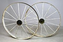 A pair of wrought iron wagon wheels with metal spokes, paint