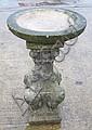 A reconstituted stone bird bath with a circular