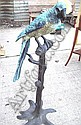 A 20th century bronze model of a macaw on a