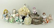 A quantity of porcelain pin cushion dolls, early 2