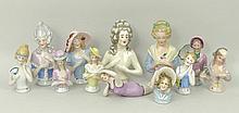 A quantity of porcelain pin cushion dolls includin