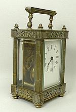 A Victorian brass carriage clock, enamel dial bearing Roman numerals, the case with embossed foliate