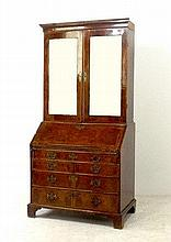 A George II walnut and crossbanded bureau bookcase, the upper section having two bevelled mirrored d
