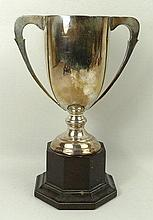 A silver twin handled trophy, Birmingham 1928, 10.49toz, on an octagonal bakelite socle.