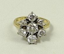 An 18ct gold and diamond seven stone ring of double triform design, the central stone approximately