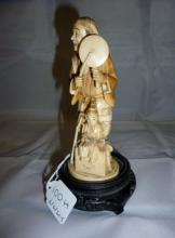 A Chinese ivory figure of a man and child on a carved wooden base est: £150-£250