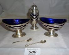 A pair of silver pedestal boat shaped salts with pierced decoration and blue liners with matching pepper pot Birmingham 1906 and two silver salt spoons est: £80-£120