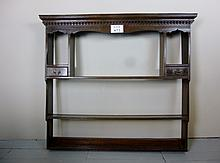 An 18c 'waterfall' set of oak wall shelves with moulded pediment and dentil course above a carved frieze; two display 'niches' with drawers below; three plate-rack shelves est: £100-£150