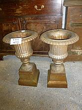 A pair of iron garden urns on stands est: £100-£150