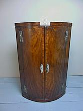 A George III bow fronted corner wall cupboard in mahogany est: £100-£150