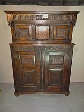 A Charles I carved oak court cupboard with a moulded pediment, projecting frieze with fluted decoration and central 'S' scrolls; turned pendants above a recessed cupboard enclosed by a pair of doors with carved geometric designs and flanking a