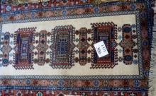 A 20c part wool rug on cream ground (150 x 90 cm approx) est: £40-£60