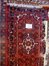 A 20c wool rug on red ground (130 x 70 cm approx) est: £30-£40