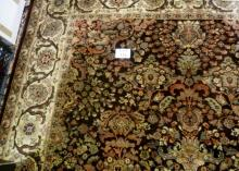 A large wool carpet on brown ground (350 x 245 cm approx) est: £200-£300