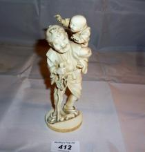 An oriental ivory carving of an old man carrying a child signed est: £120-£160