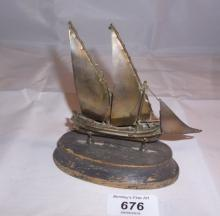 A model of a white metal yacht on a wooden base stamped 917 est: £50-£70