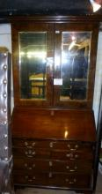 An 18c walnut bureau bookcase with double mirrored doors over a fitted bureau interior and drawers beneath (slightly a/f) est: £170-£250