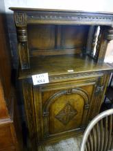 A fine 17c style oak slim cupboard with raised back over a carved cupboard door est: £100-£150