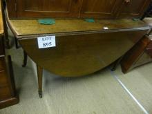 A George III mahogany oval drop leaf dining table terminating on brass casters est: £100-£150
