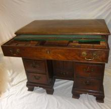 A superb mid 18c mahogany knee hole desk with a pull out fitted drawer and slide over a centre sliding cupboard and drawer flanked either side by three drawers, brass swan handles and bracket feet est: £800-£1,200