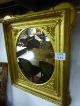 A 19c decorative gold wall mirror in good condition with central oval mirror est: £150-£250