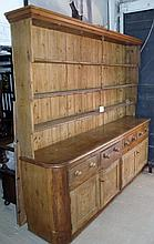 A large Victorian pine dresser with panelled open plate rack above four drawers and cupboards est: £400-£600