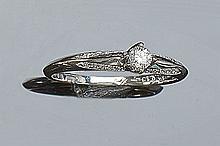 Anillo en oro blanco, con un brillante central ( 0,13 ct aprox) en garras, y bandas de brillantitos (20 bts: 0,09 ct aprox) laterales. Nº anillero: 14.