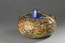 DAGE L.     Vase ovoïde à corps légèrement aplati en céramique émaillé bleu, brun et orange. Décor d'une    monture en métal doré à décor branche de noisetier.    Signé.    Haut. 15 cm  Largeur 21 cm