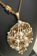 ROGER SCEMAMA Collier en métal doré et strass retenant un pendentif orné de perles nacrées et strass de couleurs    Longueur : 54cm