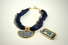 FREY WILLE Colier cordon bleu avec un pendentif en métal doré émaillé bleu à motif egyptien (on y joint une broche émaillée bleu à décor d'éléphant)
