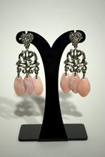 CHRISTIAN LACROIX Une paire de boucles d'oreilles en métal argenté à pampilles de nacre rose, on y joint une paire de créoles retenant des perles fantaisies    Hauteurs : 8 cm et 6 cm