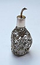 Petit flacon de forme trilobée, monture ajourée en argent à décor de fleurs de poirier -  bouchon à bec verseur -  Travail étranger début 20ème -   Hauteur : 11cm -  Poids brut : 99,9g (petits manques)