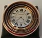 CARTIER Pendulette réveil modèle Trinity en métal de trois tons, diamètre : 7 cm - Trinity metal clock, diameter : 2,7 in.