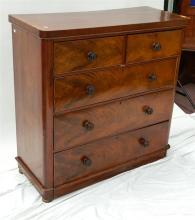 An antique flame mahogany chest of five drawers