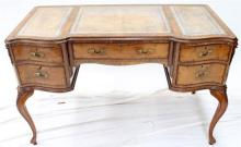 A Louis XVI Style Five Drawer Desk with Leather Inset Top