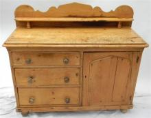 A baltic pine three drawer, single door sideboard with gallery top