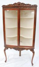 A glazed two door mahogany corner display cabinet on cabriole legs, early 1900's