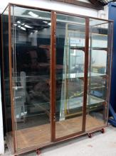 A wooden framed glass display cabinet with three shelves & one central door