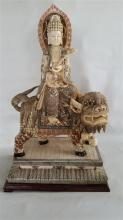 A Carved Figure of Guanyin Riding a Fu Dog